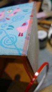 doppelseitiges Klebeband an den Schubladenrändern anbringen, damit das Satinband nicht verrutscht.